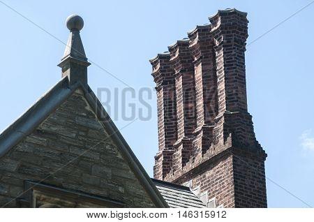 Old vintage brick chimneys on roof of old building