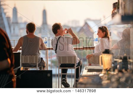 THAILAND-FEBRUARY 5 2016 : Unidentified Traveler enjoying take a photo sunset time at top view bar and restaurant by the temple of dawn or wat arun a beautiful backdrop.