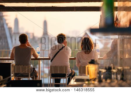 Travelers enjoying take look at view sunset time at top view bar and restaurant by the temple of dawn or wat arun a beautiful backdrop.