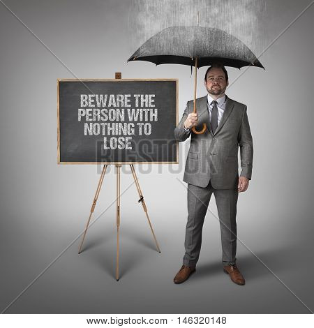 Beware the person with nothing to lose text on blackboard with businessman and umbrella