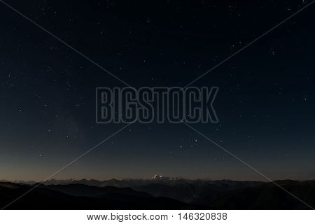Beautiful night landscape with stars in the night sky against a background of the contours of mountains shot with a long exposure
