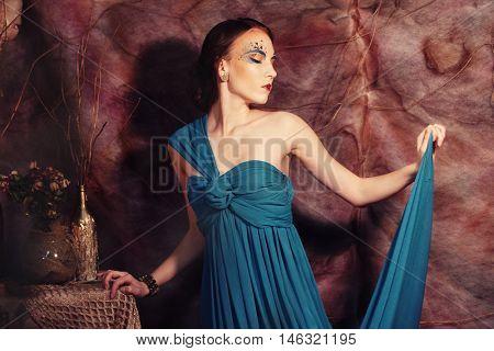 elegant sensual young woman in blue dress