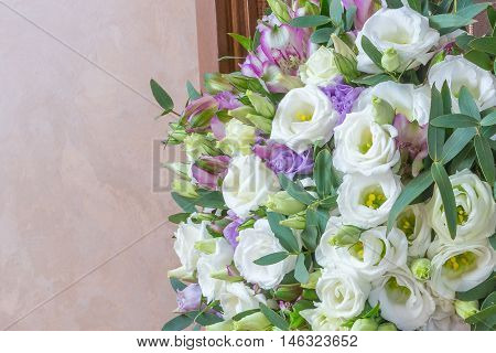 Wedding bouquet of white flowers eustomy purple alstroemeria and green eucalyptus leaves on a beige background.