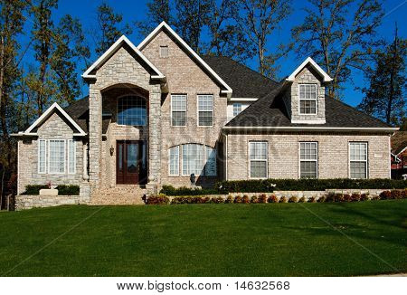 beautiful two-story home with beautiful cloudless blue sky in background