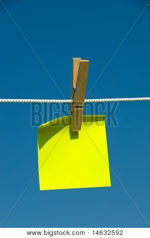 Yellow sticky note on a clothesline with blue sky background