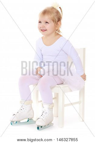 Cute little girl , a future figure skater, sits on a chair in a White sports dress and figure skates on two skids-Isolated on white background