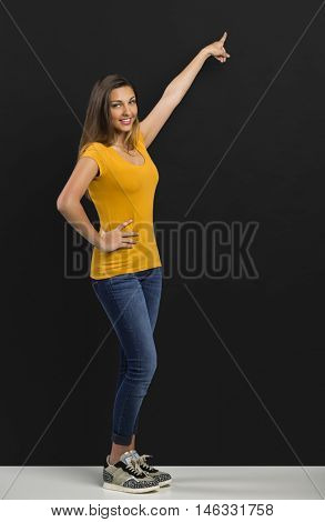Beautiful woman standing in front of a dark board and pointing