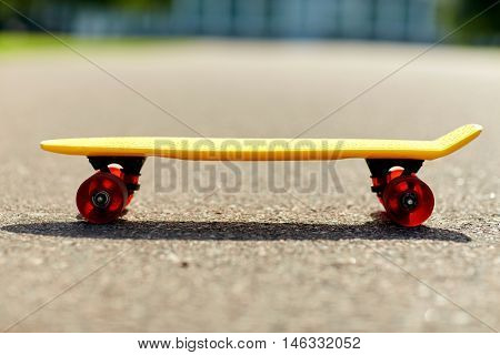 skateboarding, leisure, extreme sport and equipment concept - close up of short modern cruiser skateboard on road