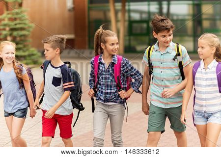 primary education, friendship, childhood, communication and people concept - group of happy elementary school students with backpacks walking and talking outdoors