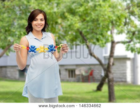 pregnancy, motherhood, people and expectation concept - happy pregnant woman holding rattle toy over summer garden and house background