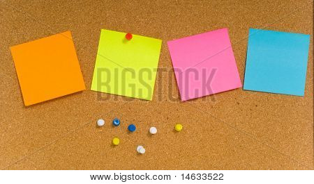 Blank sticky notes on a brown corkboard or bulletin board with colored push pins. add your own text