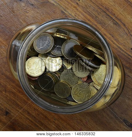 Euro cents in a glass jar as piggy bank on wooden table