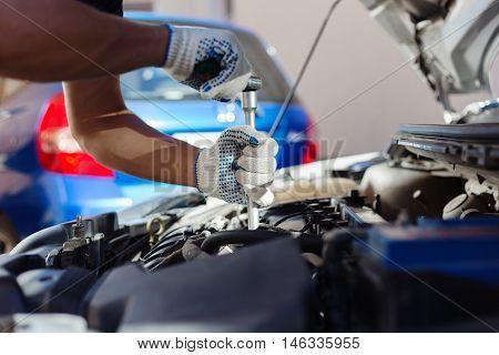 Mechanic working in auto repair garage. Car maintenance.