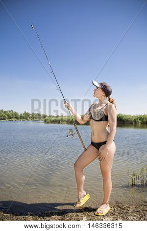 Sexy redhead young woman on spinning fishing