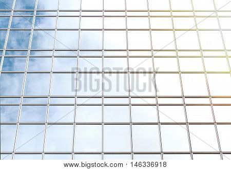 Facade of an office building with reflected sky and sun