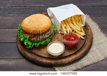 Fast food restaurant dish. American meat burger and potato chips on wood. Takeaway composition. French fries, hamburger, mayonnaise and ketchup sauces on round wooden desk.