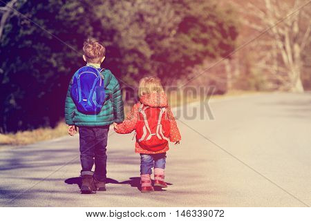 kids go to school - little brother and sister with backpacks walking on the road