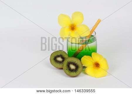 Two tone of kiwi juice served with halves kiwi and yellow flower on white background.