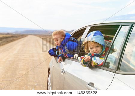happy little girl and boy travel by car on the road