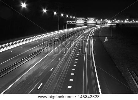 The famous Snelweg motorway in the Netherlands at nighttime withstreaks of light from cars in time lapse exposure