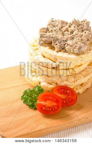 slices of puffed rice bread with fish spread on wooden cutting board
