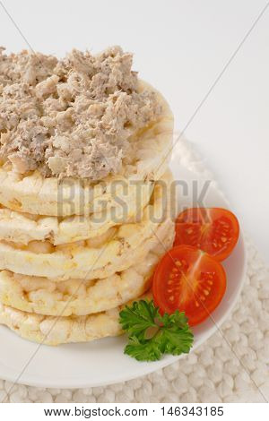 slices of puffed rice bread with fish spread on white plate