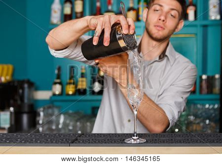 Young handsome barman in bar interior pouring alcohol cocktail drink into glass. Professional bartender at work in night club. Service industry occupation