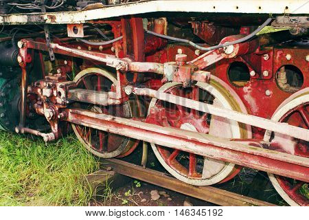 Old, vintage locomotive which stands on the rails. Rusty and dirty train wheels close up. The train made in the distant past.