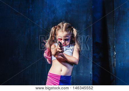 Halloween theme: Little girl pointing at toy gun on dark blue background