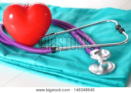 A stethoscope shaping a heart and a clipboard on a medical uniform, closeup.