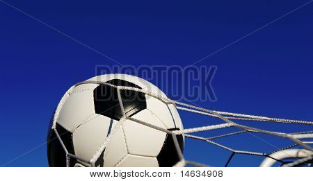 A traditional soccer ball or football in a goal net in front of a blue sky