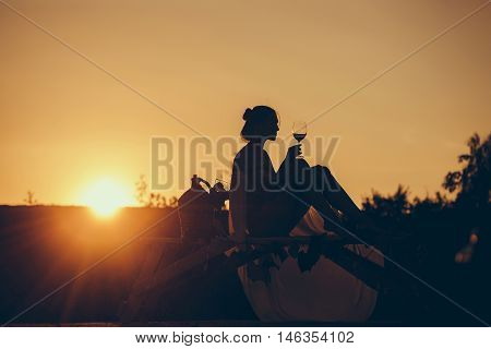 Silhouette of slim girl young woman female model sommelier with wine glass and wicker bottle on nature over beautiful sunset