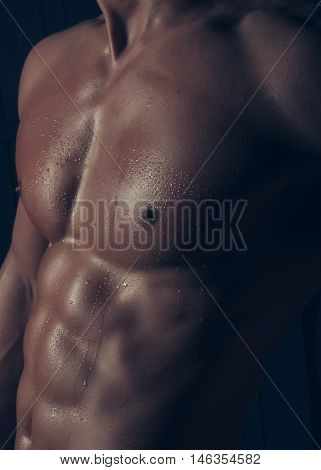 Sexy strong bare torso with abs and muscular male chest on black background