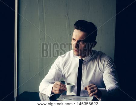 Man young handsome elegant model wears white shirt black skinny necktie sits at table holds cup of coffee and looks away indoor on grey background