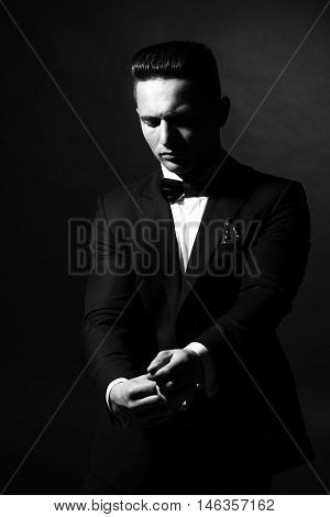young handsome gentleman in fashion black suit white shirt and bow tie in studio black and white