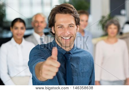 Businessman giving thumb up to camera in front of colleagues. Successful businessman showing thumbs up sign and looking at camera. Young happy manager with business team.