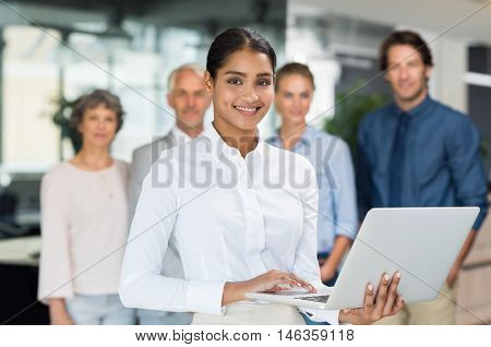 Beautiful smiling business woman using laptop in office. Portrait of young happy business woman using computer. Portrait of smiling multi ethnic businesswoman looking at camera with her teamwork.