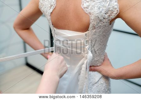 Bridesmaid is lacing white wedding dress for beautiful bride. Beauty model girl in bridal gown for marriage. Female portrait. Cute lady indoors