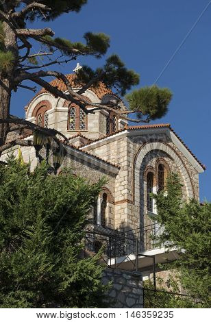 The Orthodox temple the Cathedral the Church with the tiled orange roofs and stone walls in the Byzantine style with the pine tree on blue sky background in Greece a Sunny day