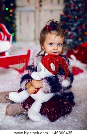 Happy beautiful girl Princess in white dress hugging a Teddy bear on the background of the Christmas tree and night lights . Happy New Year little Princess