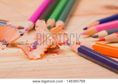 Wooden colorful pencils with sharpening shavings, on wooden table