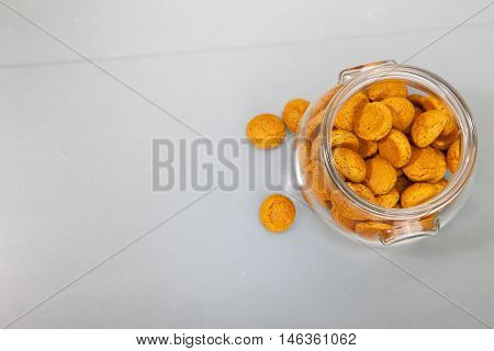 Traditional Dutch candy pepernoot in glass jar on grey background