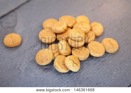 Pile of Dutch candy pepernoten on black wooden background