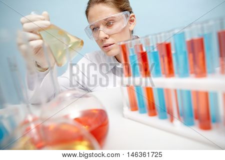 Portrait of woman chemist holding beaker with chemical liquid