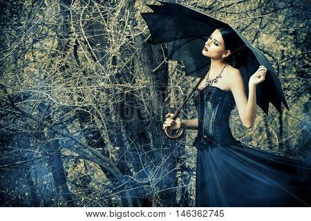 Magnificent brunette woman wearing long black dress walking in a mystic forest. The old times, the Gothic style. Fashion.