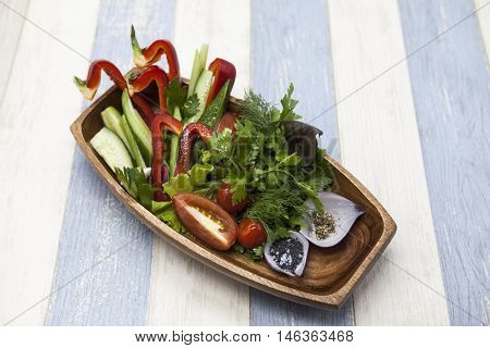 Fresh vegetables on a wooden plate. Red pepper, tomato, cucumber, radish, parsley, dill healthy diet
