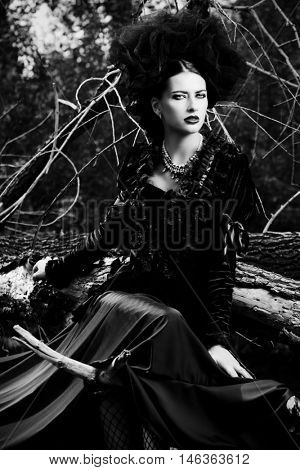 Gorgeous gothic woman wearing long black dress posing in a mystic forest. The old times, the Gothic style. Fashion.