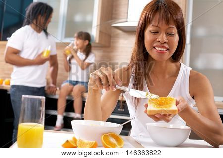 Young woman eating bread with jam with her family on background