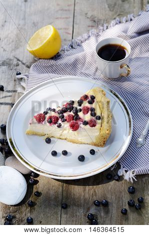 Sunny Photo with a morning breakfast in rustic style. Cheesecake raspberries and blueberries on wooden table.