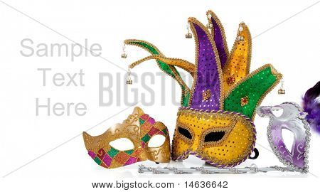 Several mardi gras masks with gold, purple, green and white with copy space on a white background